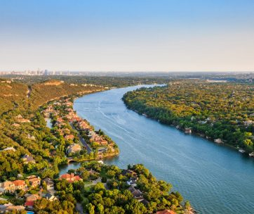luxury homes on Colorado River near Austin TexasAerial view of Luxury homes on Colorado River in Mount Bonnell district in hill country near Austin Texas. City of Austin skyline in distance.