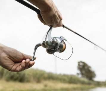 Up close of man using fishing rod and reel